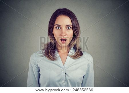 Stunned Woman In Blue Shirt Standing With Mouth Opened And Looking At Camera On Gray Background