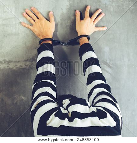 Rear View Of Unidentified Prisoner In Prison Stripped Uniform Standing Near The Wall With Hands Up I