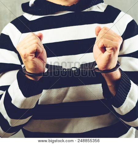 Front View Of Unidentified Prisoner In Prison Stripped Uniform Standing In The Dark Interrogation Ro