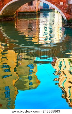 Venetian mirror - Houses, blue sky and small bridge reflect in the water of canal. Venice in water reflections