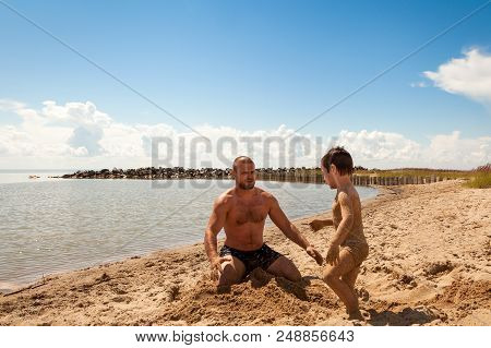 Joyful Father And Son  Spend Time Together On The Beach. Happy Playful Family In Summer Vacation . F