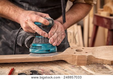 Close up of an young man builder carpenter equals polishes wooden board with a  random orbit sander  in the workshop poster