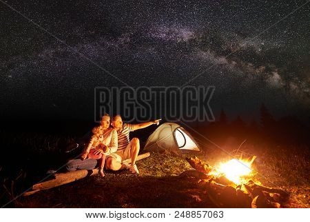 Camping In Mountains At Night. Tourist Family Resting In Front Of Illuminated Tent And Burning Bonfi