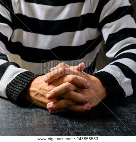 Close-up Of Unidentified Hands Of A Prisoner In Prison Stripped Uniform Sitting On The Chair In The