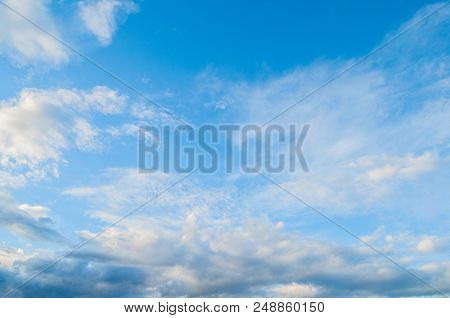 Blue Picturesque Sky Landscape - Dramatic Clouds Lit By Evening Sunlight. Picturesque Blue Sky With