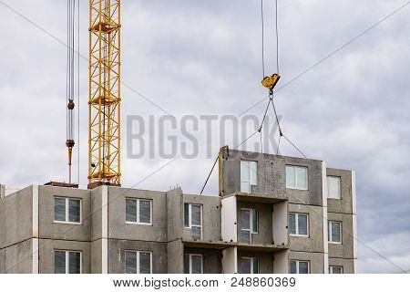 Construction Site. Construction Cranes And Apartment Building Under Construction Against Blue Sky. C