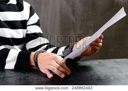 Unidentified Prisoner In Handcuffs In Prison Stripped Uniform Sitting On The Chair In The Dark Inter
