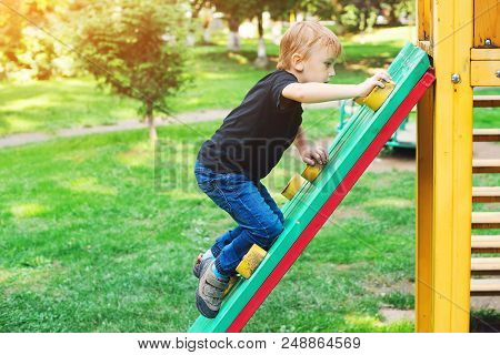 Happy Kid Climbing On Outdoor Playground. Little Blond Boy Having Fun Outdoors. Summer, Spring And A