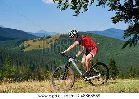 Strong Athletic Sportsman In Professional Sportswear Cycling A Bicycle In High Grass Under Big Green