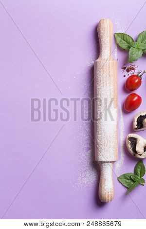 Baking Background With Copy Space On Purple Surface For Your Text. Top View. Traditional Ingredients