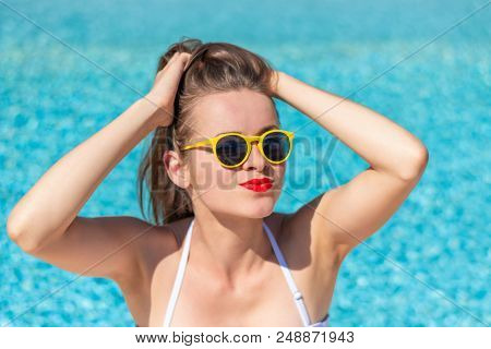 Summertime In Pool. Young Woman With Yellow Sunglasses In Pool.