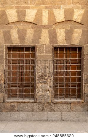 Two Similar Adjacent Wooden Closed Windows With Iron Grid Over Decorated Stone Bricks Wall, Medieval