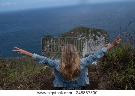 Back view of sitting on the cliff and raising hands over beautiful Kelingking Beach cliffs background in Nusa Penida, Bali, Indonesia