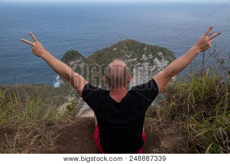 Back view of man sitting on the cliff with raised hands over beautiful Kelingking Beach cliffs background in Nusa Penida, Bali, Indonesia
