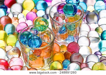 two glass beakers with hydrogel balls, transparent round shapes poster