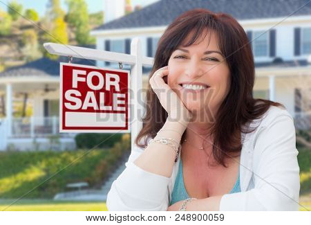 Middle Aged Woman In Front of House with For Sale Real Estate Sign In Yard.