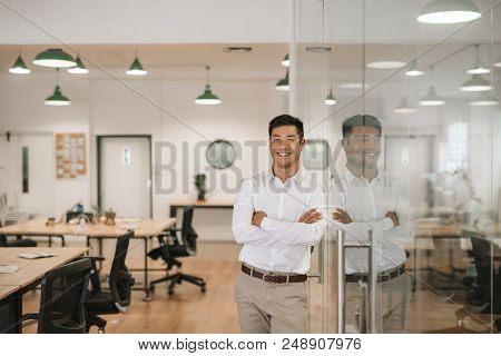 Successfull Young Asian Businessman Smiling Confidently While Leaning Against A Glass Wall With His