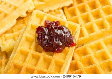 Close-up Of Homemade Fresh Brown Waffles. View To Stacked Wafles With Tasty Jam. Bakery And Food Bac