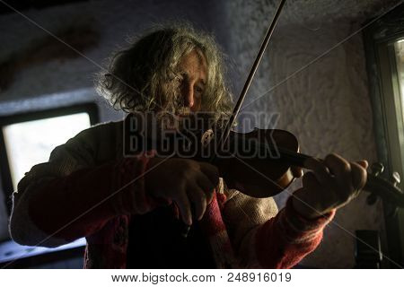 Elderly Male Musician With Tousled Long Hair Playing A Classical Violin At Home In A Head And Should