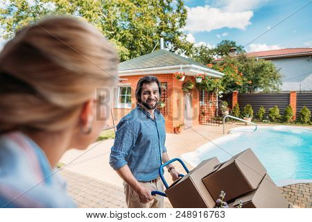 Smiling Man With Handle Tray With Cardboard Boxes Looking At Wife On Porch Of New House, Moving Home