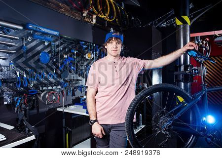 Small Business And Bicycle Transport Service. Portrait Of A Young Man In A Cap Posing Against The Ba