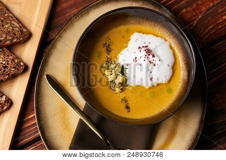 Hot Pumpkin Cream Soup With Cream And Pumpkin Seeds, Coconut Milk, Green Oil, Sprouts Of Lentils In