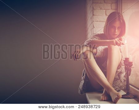 Beauty On The Window Sill. Pretty Woman Light Candle On Window Sill. Fashion Woman With Makeup And L