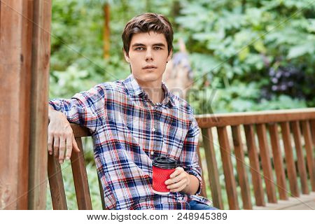 Young Smiling Man Wearing Colorful Shirt Is Holding Red Cup Sitting On The Bench In The Summerhouse