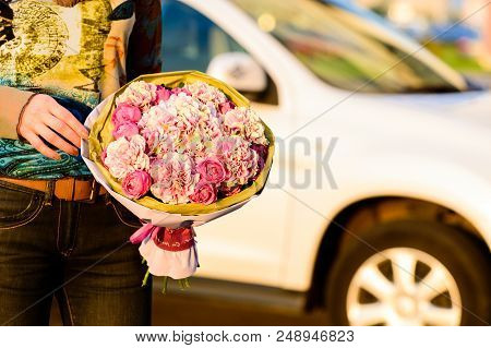 Hands Of Young Unidentified Woman Holding A Beautiful Bouquet Of Pink Peonies Flowers Wrapped In Pap