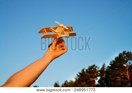 Unidentified Woman Holding A Wooden Airplane Against Blue Sky. Concept Of Dreaming, Travelling And T