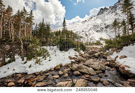 Snowy landscape with rocks and mountains in snow around at autumn with cloudy sky. Rocky Mountain National Park in Colorado, USA.