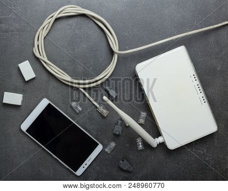 Wi-fi Router And Cable For Connection, Connectors, Adapters And Smartphone On Gray Background