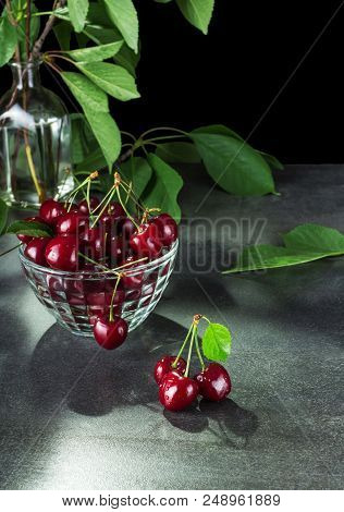 Ripe Red Cherries With Tails In Glass Bowl, On Grey Surface