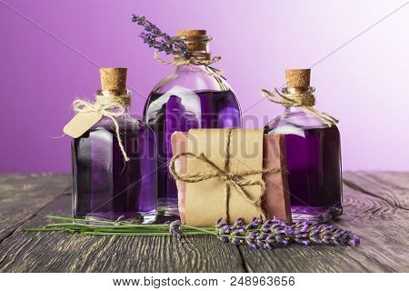 Bottles With Lavender Tincture Closed Cork, And Piece Of Soap On Old Wooden Table