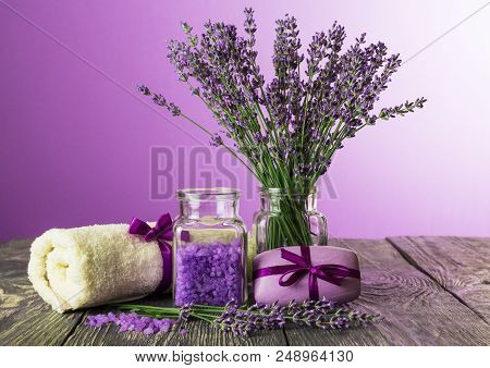 Set For Spa Treatments On Table Bouquet Of Lavender In Vase On Purple Background