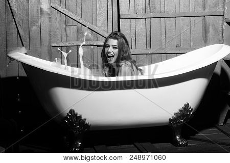 poster of woman enjoys a hot bath. Beauty fashion model portrait. One beautiful sensual playful flirtatious young woman with long hair in blue knitted cloth sitting in white bath tub playing with soap foam indoor on wooden background, horizontal picture