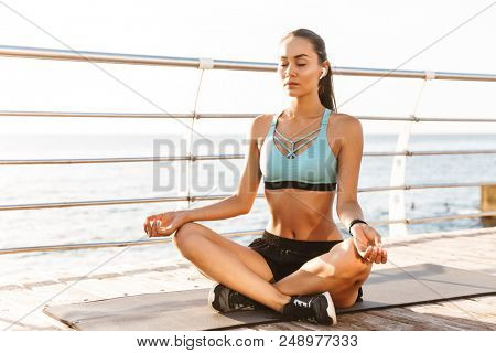 Image of sporty fitness woman 20s in sportswear sitting on exercise mat in yoga pose and meditating near seaside