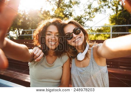 Two excited young girls having fun while taking selfie together at the park