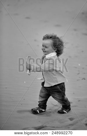 Happy Child With A Shovel. Joyful Fair-haired Kid Tiny Little Child Baby Boy In Jeans Striped Shirt
