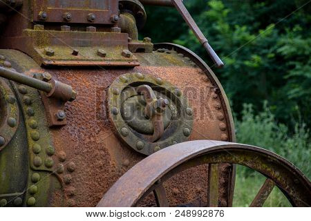Old and rustic steam train or tractor used in Serbia in 1920s and 1930s. Made in Germany. Old fashioned steamed tractor standing in a field. Old vintage steel wheel farm tractor. poster