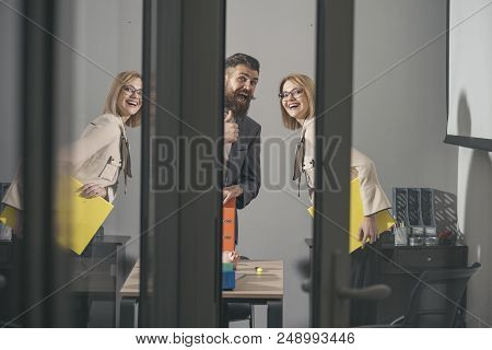 Happy Colleagues Look Out Modern Office With Glass Walls. Business Couple Smile At Meeting. Bearded