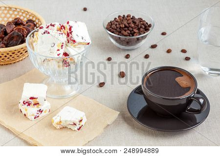 A Cup Of Black Coffee And A Few Pieces Of Homemade Nougat With Peanuts And Dried Cranberries