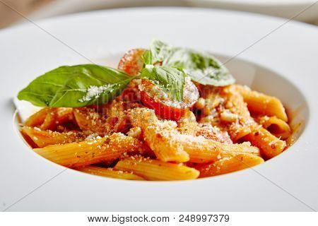 Tomato Penne Pasta Al Dente with Tomato Sauce, Parmigiano Reggiano Cheese, Cherry Tomatoes and Basil in White Plate Close Up. Traditional Italian Macaroni in Restaurant