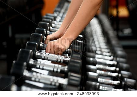 Female Hands Close Up Taking Dumbbells From Row Of Barbells In A Gym