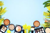 Set of decorative cosmetics for make-up Powder Rouge Eyeshadow Corrector Brushes and flowers of mimosa on blue background. Makeup Accessories Top view poster