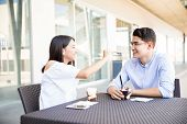 Teenage girl feeding icecream to boyfriend in cafe at shopping mall poster