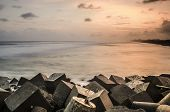 rock breaker waves, with the sunset background, taken in the glagah beach, yogyakarta, indonesia poster