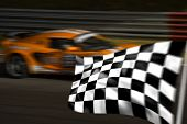 Orange racing car passing the chequered / checkered flag with motion blur poster