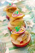 herring appetizer towers with slices of potato and apple gherkin,red onion and dill for christmas poster