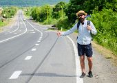 Pick me up. Hitchhiking one of cheapest ways traveling. Picking up hitchhikers. Hitchhikers risk being picked up by someone who is unsafe driver or personally dangerous. Man try stop car thumb up. poster